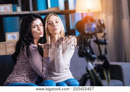 We love you. Positive delighted young women sitting together and looking into the camera while sending a kiss to their viewers