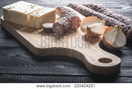 Sausages and cheese on a wooden board - Tasty meal with homemade smoked sausages from beef and pork, fresh cheese and onion, displayed on a wooden cutting board, on a rustic black table.