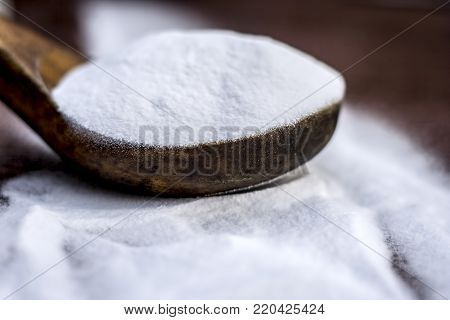 Baking Soda Or Sodium Hydrogen Carbonate In A Wooden Scoop On The Brown Wooden Surface.
