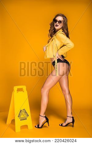 sexy woman posing in yellow leather jacket and black panties