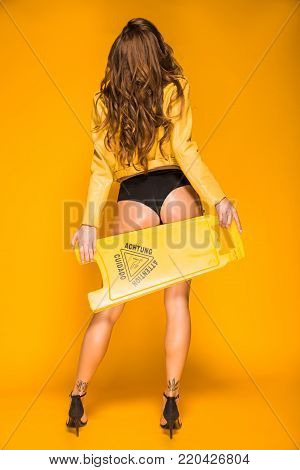 back view of sexy woman in black panties holding wet floor sign on orange