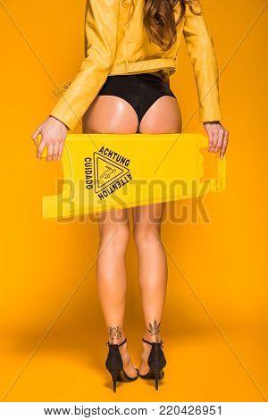 cropped image of seductive woman holding wet floor sign on orange