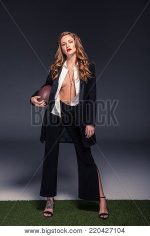 sexy woman in unbuttoned shirt and jacket holding american football ball and looking at camera