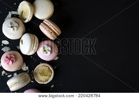 Colorful natural macarons cake, top view flat lay, copy space sweet macaroon on color dark black marble text background. Minimal concepts falling macaroons food background