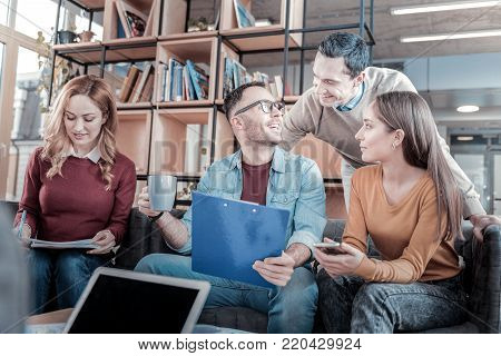Glade to see you. Young satisfied smiled colleagues sitting in the room near bookcase having fun and spending time together.