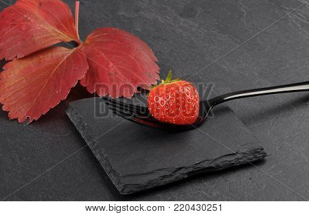 Colorful and crisp image of strawberry on fork and shale