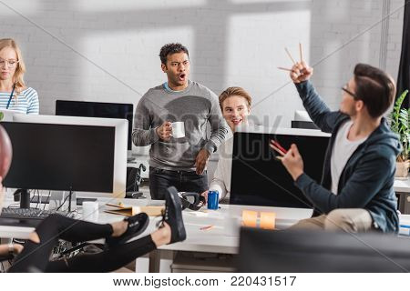 man threatens by pencils to his impressed colleagues at office