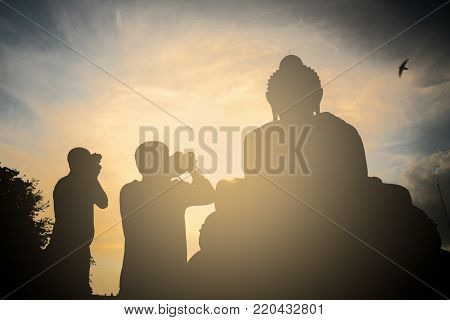 Silhouettes of two photographers of traveler making photos of a larger buddha in Thailand. Travels in Asia.