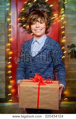Happy child boy stands on the porch of a house decorated for Christmas and holding a gift box. Time for miracles.