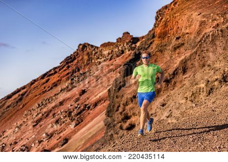 Trail runner man athlete ultra running in mountain rocky path in nature. Volcano mountains backcountry landscape. Fitness and sports active lifestyle.
