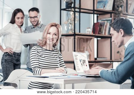 Work and friends. Smiling cute occupied lady sitting in the room by the table looking straight and writing.