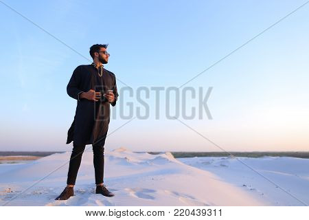Shooting image of  smiling swarthy Arab, who smiles broadly with teeth and looks into camera. Modern sheikh man stands right in middle of desert and holds hands on belt, enjoying warm day in large desert with white clean sand and clear blue skies on summe