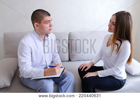 Charming girl tells about medical history of male psychiatrist with friendly smile on face, listens and writes with pen to medical card and prescribes course of treatment sitting on light sofa in hospital's office on background of light gray wall