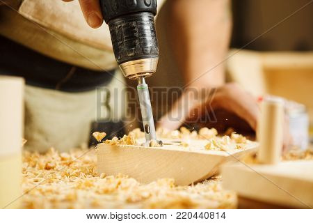 Wood boring drill in mans hand drilling hole in wooden bar, electric instrument works with wooden surfaces, equipment for construction different materials necessary in carpentry
