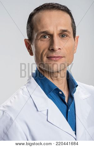Patients health. Earnest handsome male doctor posing on the isolated background while working and looking at the camera