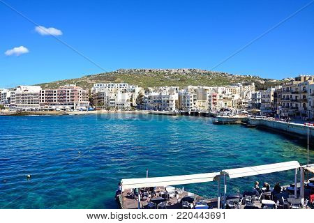 MARSALFORN, GOZO, MALTA - APRIL 3, 2017 - Elevated view of the town and beach with a pavement cafe in the foreground, Marsalforn, Gozo, Malta, Europe, April 3, 2017.