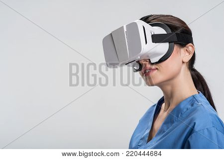 Modern approach. Happy dreamful female doctor  accustoming to VR glasses and smiling  while  examining virtual reality