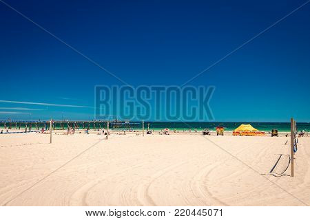 Glenelg, South Australia - February 28, 2016: People with surf life saving patrol at Glenelg beach viewed from Beach House on a bright summer day