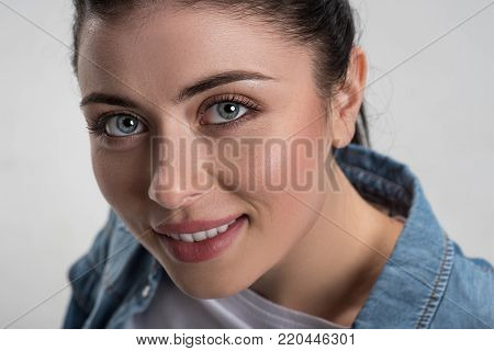 Charming smile. Close up of ambitious happy female face when woman smiling posing on the  grey background while  gazing at the camera