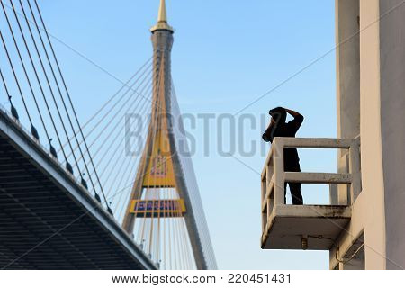 A photographer has shooting photo of  Bhumibol Bridge with blue sky in the evening at Bangkok Thailand.