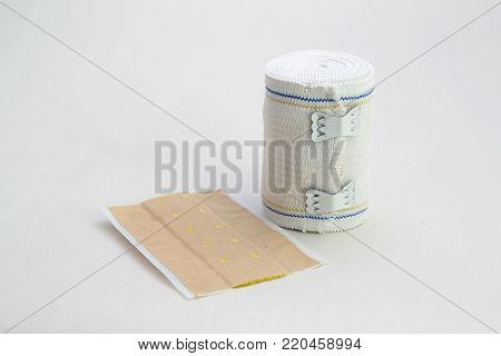 A roll of elastic bandage for sprains and a patch on white background