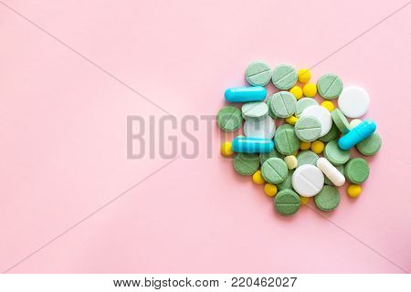 Opioid Pills. Opioid epidemic and drug abuse concept. Different tablets, pills, capsule on a pink background.  Heap mix therapy drugs. Copy space