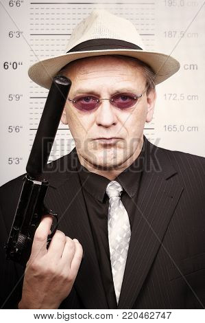 Older retired rent killer portraited with silenced pistol in front of mug board