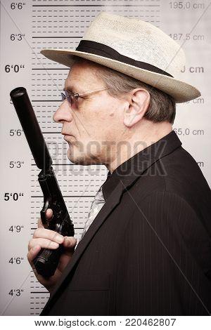 Older rent killer portraited with silenced pistol in front of mug board