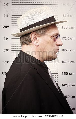 Older bad man portraited in sunglasses and hat in front of mug board