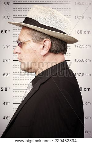 Older man portraited in sunglasses and hat in front of mug board