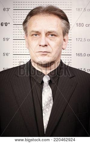 Older man in suit portraited on police station in front of mug board