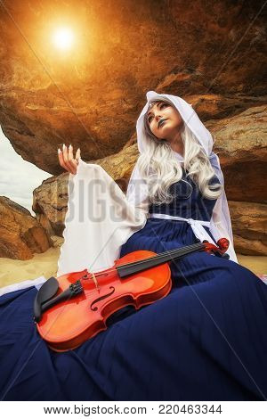 Beautiful Girl In an elf costume reaches out to the light. Elf with a violin near the rock.