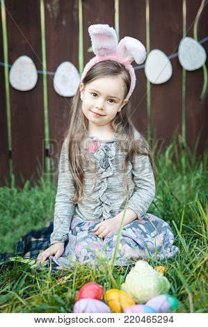 Little girl with rabbit ear Easter celebration. Laughing children at Easter egg hunt. Cute toddler girl with easter bunny ears sitting on colorful plaid outdoor and celebrating holiday