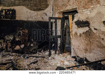 Burned room interior in apartment house. Burned door and charred walls.