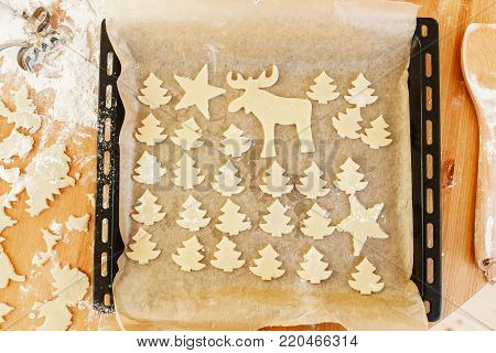 Christmas cookies gingerbread on baking tray. Shapes of deer and firtrees. Delicious sweet biscuit. Top view. Winter holidays, food and celebration concept