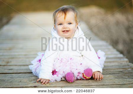 Adorable baby on wooden bridge