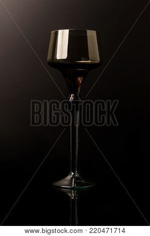 A large glass of dark glass isolated on the black background.