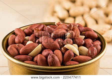 Bronze bowl of peeled peanuts and peanuts in nutshell on wooden table