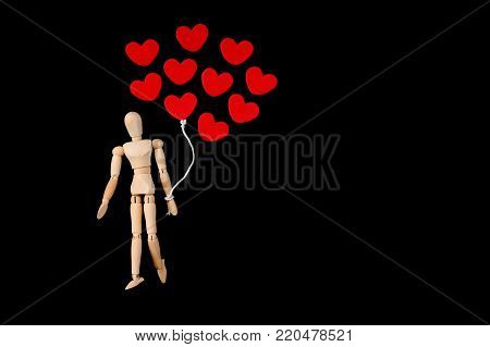 Wooden man figure holding red heart balloon. Wooden human dummy on a black background with copy space for your text. Concept for valentine's day celebration or couple of love.
