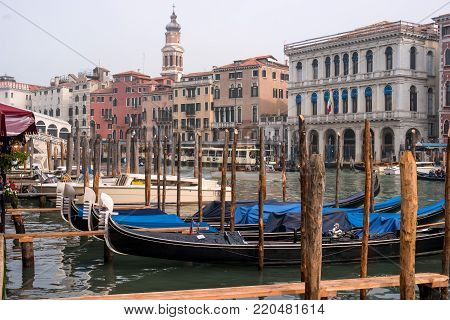 Venice, Italy - October 13, 2017: Gondolas in Venice. The gondolas are moored at the mooring posts. In the background of the house along the Grande Canal.