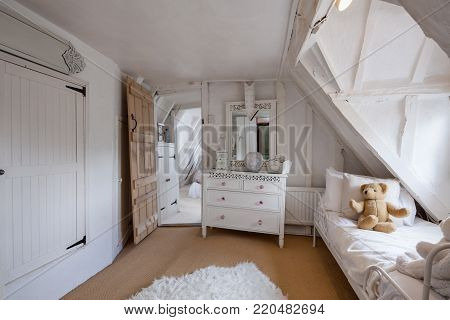 Beautifully decorated bedroom within 16th Century English cottage decorated in shades of white featuring sloping floors and misaligned doorways, chest of drawers, childs daybed with teddy bear mirror and adjoining room