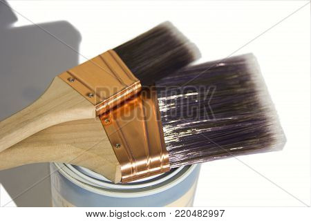 Two high quality synthetic paint brushes sitting on a tin with an white isolated background.