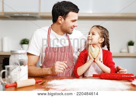Portrait of handsome affectionate father embraces her little daughter, make cookies together, being in good mood. Domestic atmosphere. Baking concept. Friendly family. Childhood concept