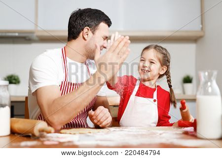 Successful small adorable child and her affectionate father express their agreement between each other, keep hands together, sit at kitchen table, bake delicious apple pie for family on supper