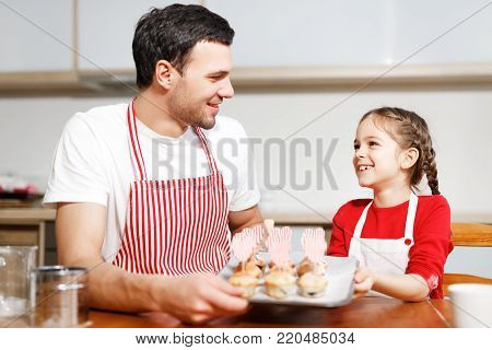 Indoor shot of handsome man wears striped apron and his small pretty female kid hold hand made cakes, rejoices successfully done work on kitchen, being in high spirit, happy spend time together