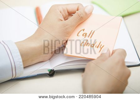 Hands holding sticky note with Call daddy text