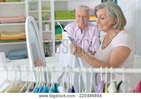 Senior couple choosing clothes in a shop