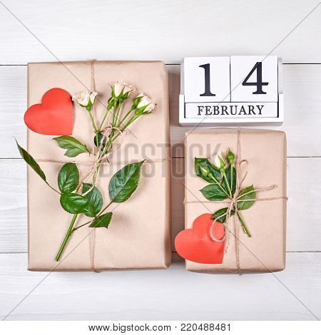 Top view of wooden block calendar with february and gift boxes wrapped in kraft with fresh roses and hearts on wooden table. Sale, shopping. Greeting card for Valentines Day, flat lay. Love concept