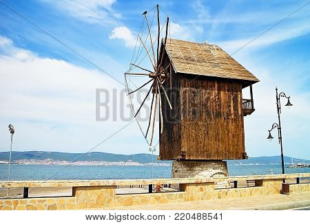 Windmill and sky in Nessebar town. A wooden windmill at the entrance to the Old town of Nesebar.