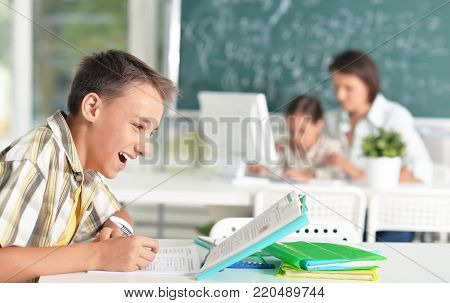 Pupil studying lessons in computer class with blurred teacher and learner on background